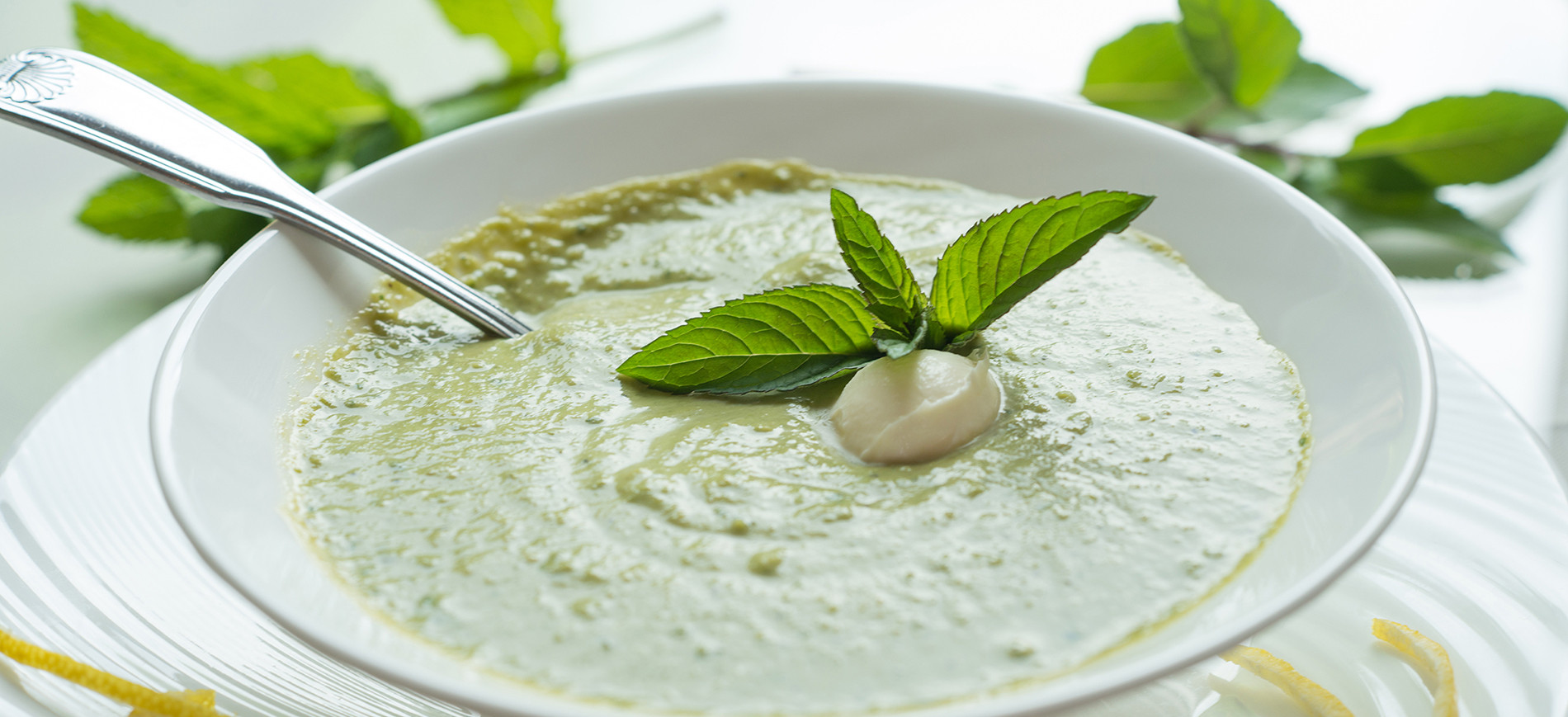 Minted pea soup with mint garnish in white bowl