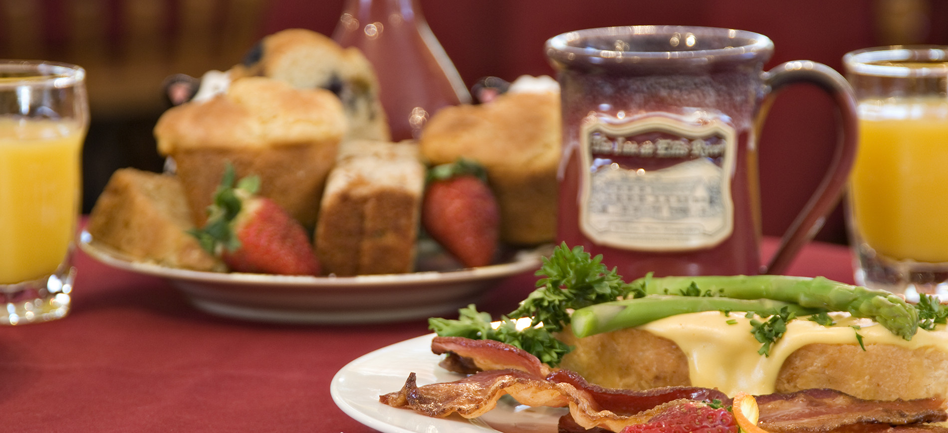 plate with muffins & strawberries & red coffee mug behind plate of bacon & eggs with asparagus