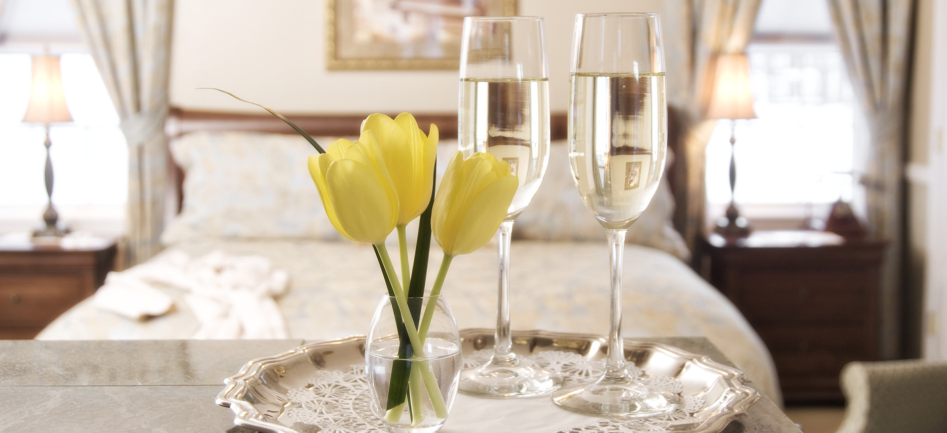 Silver tray with three yellow tulips in vase, two glasses of champagne with bed behind