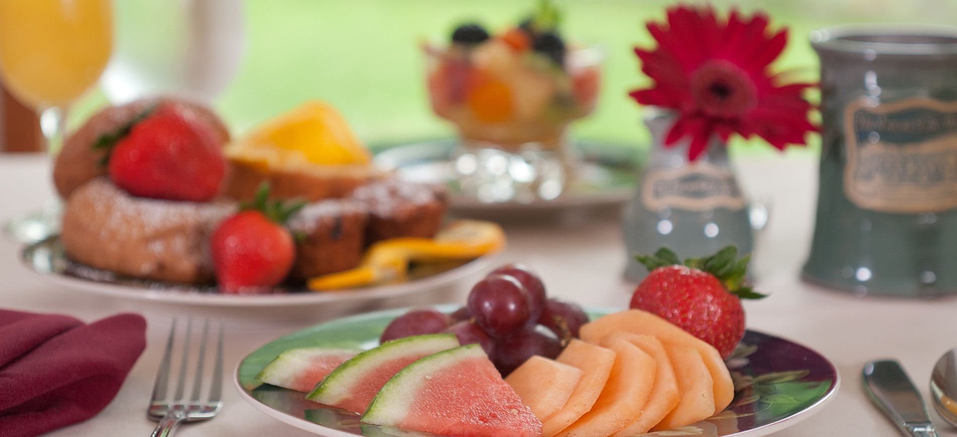 OJ, plate of muffins with strawberries, melon & grape plate in front, fruit cup at rear, vase with red gerber daisy, coffee mug