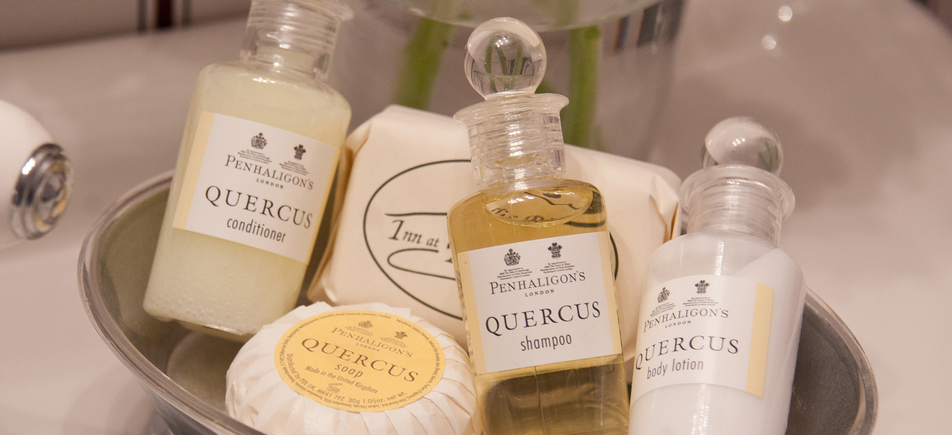 bottles of Quercus bath produces & round soap in silver dish