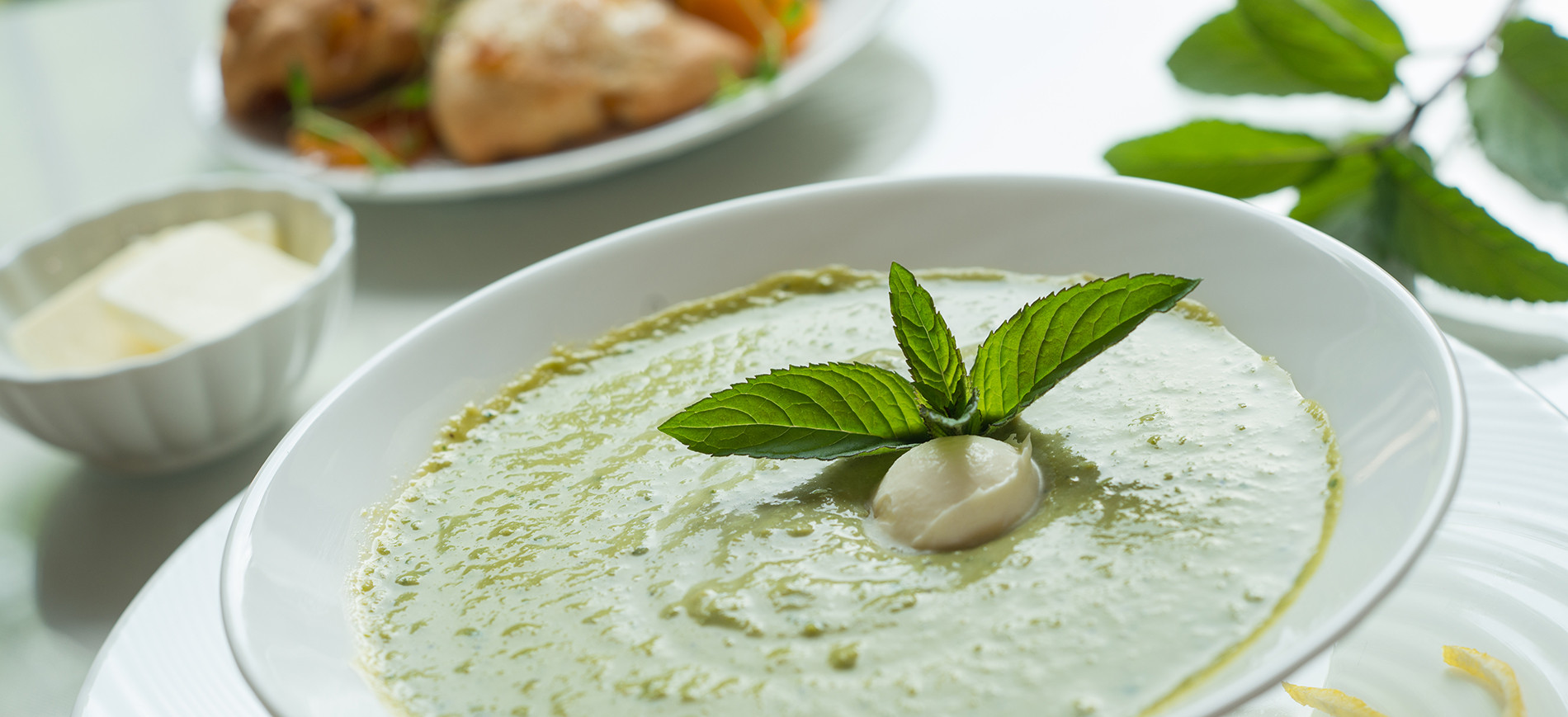 white bowl of pea soup garnished with mint