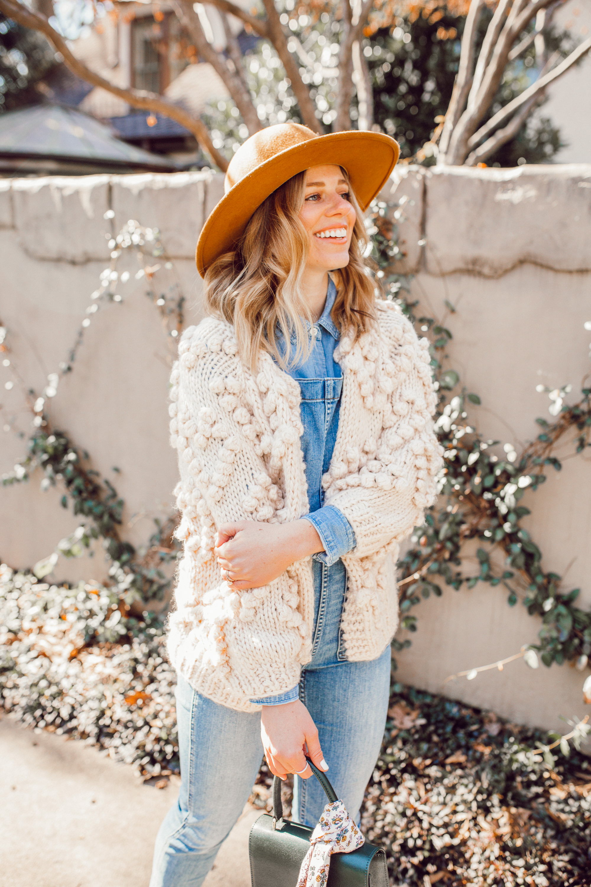 The Importance of Buying Pieces You LOVE - Even If Trendy featured on top US life and style blog Louella Reese| Image of a woman wearing Chicwish Knit Your Love Cardigan, Madewell Overalls, Yellow Wool Hat, Ariat Two24 Wilder Boots, and Neely & Chloe Ladylike Handbag.