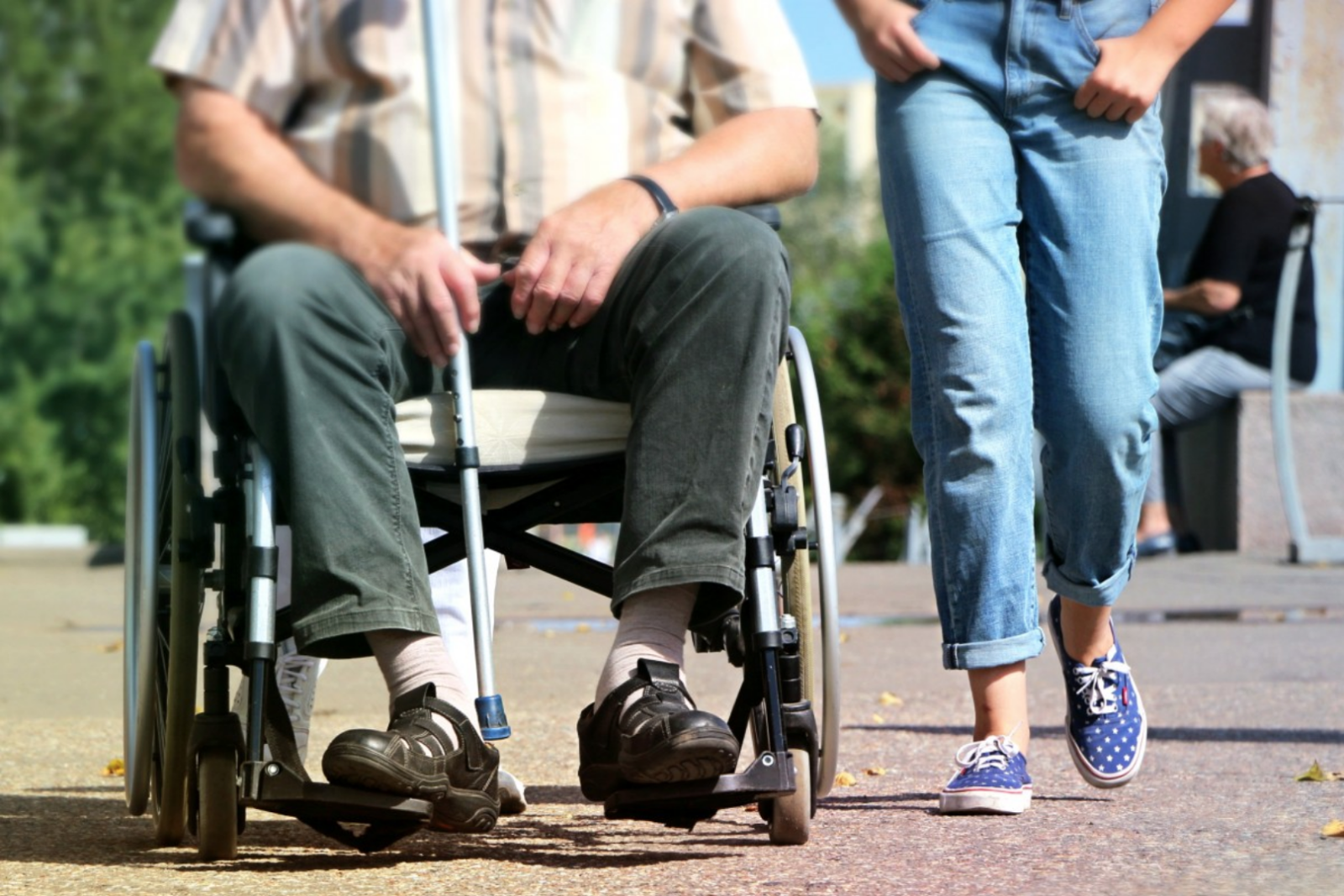 A senior citizen in a wheelchair being accompanied by a caregiver.
