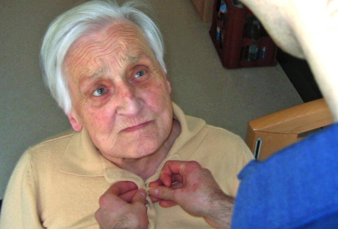 A senior citizen receiving help in getting dressed