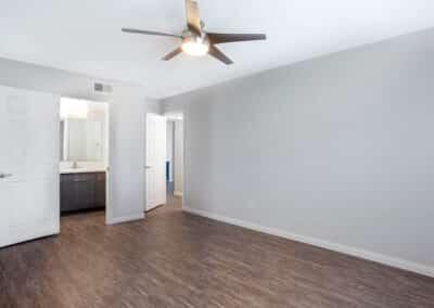 Open door showing the open space wooden floor, ceiling fan and bathroom