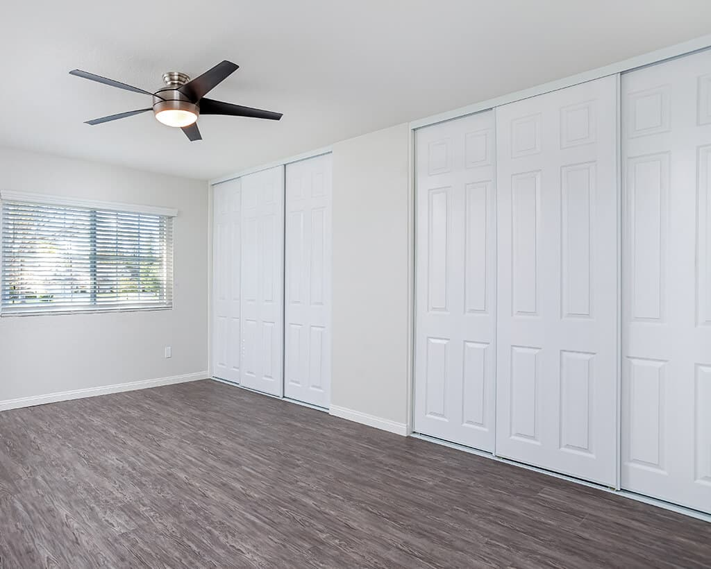 Master bedroom apartment with ceiling fan and wood flooring