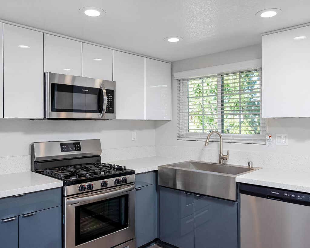 kitchen with stainless steel appliances and white cabinets and countertops