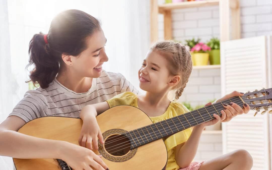 Mother and daughter having fun playing guitar