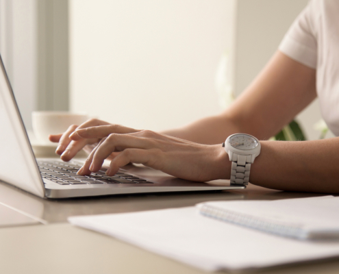 Blog Hero Close up image of womans hands typing on laptop at workplace. Businesswoman with white wristwatch on hand work