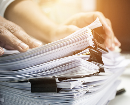 Document Automation Businessman hands searching information in Stack of papers files on work in office business report