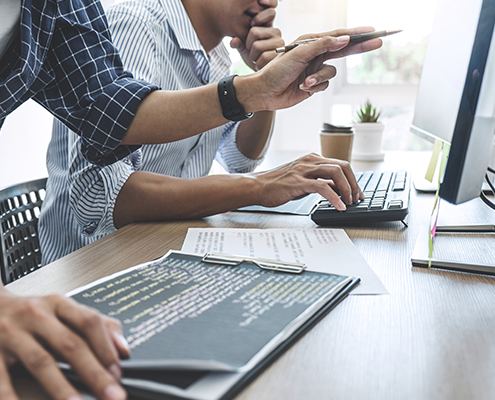 Remote Monitoring Two professional programmers cooperating at Developing programming and website working in a software d