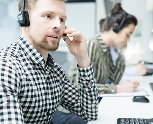 vCIO Portrait of young man wearing headset working with group of help desk operators sitting in row and talking to clien