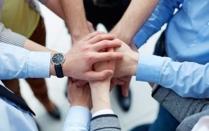 This picture shows many hands joined together to show partnership, trust and collaboration about Computer Pros Today