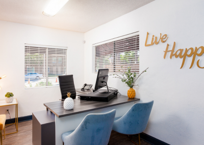 Office with Office Equipment and Live Happy posted on the wall
