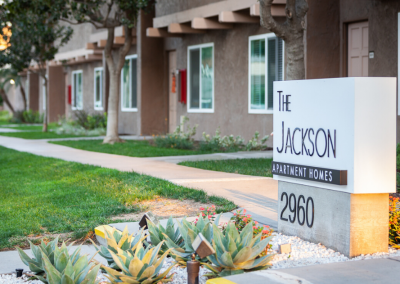 The Jackson Apartment Homes Sign Monument with green plants