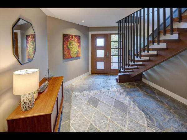 main entry with stone floors and custom door