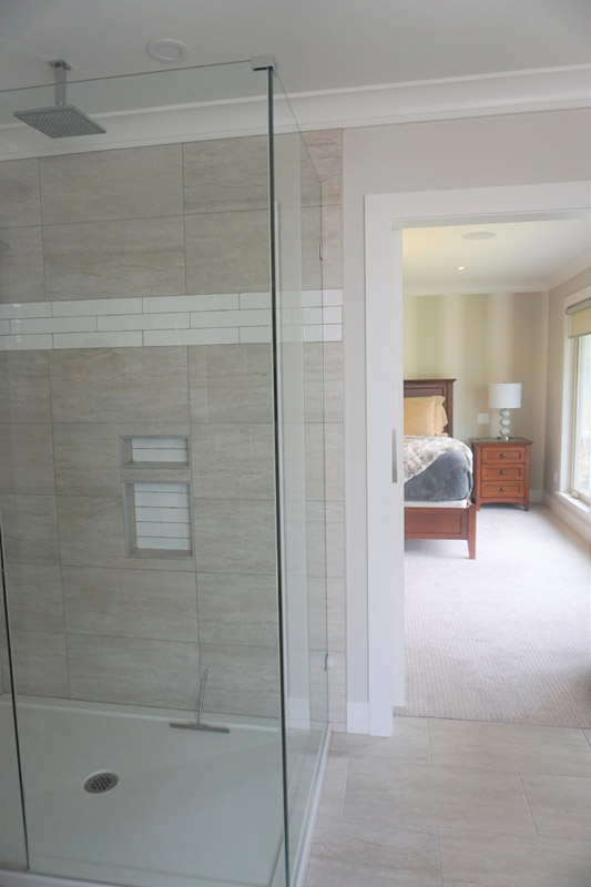 Tiles flow from the floor into the walk in shower walls.