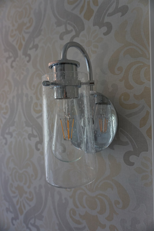 Wall sconces add warm and relaxing light to the bathroom.