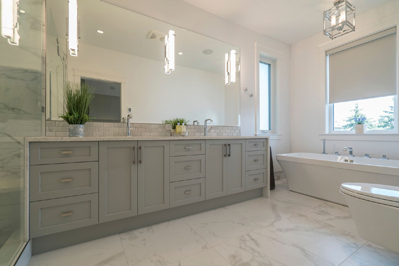Stunning master ensuite with waterfall countertop on both sides that encases the cabinetry with style. With the added beauty of a custom accent Foilage be bop white glass mosaic from Artistic tile.