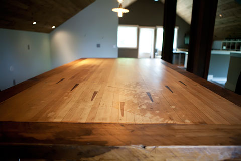 Custom from top to bottom this solid maple table top was salvaged from a bowling alley that was up for demolition.