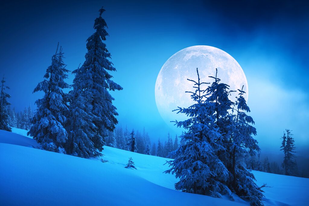 Moon over snowy mountains at night