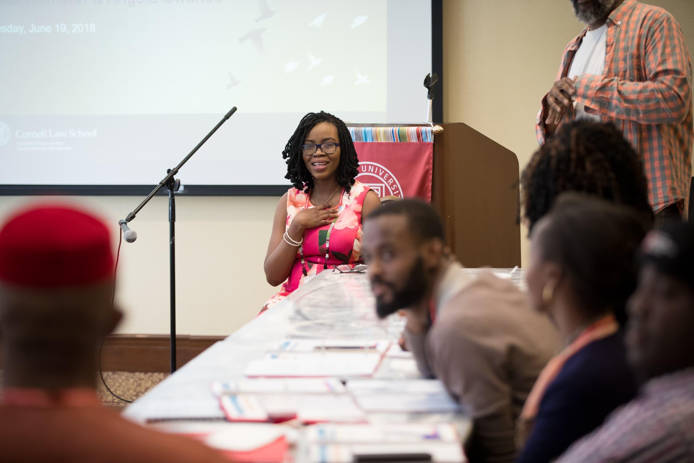 Une femme portant des lunettes et une robe rose parle à l'avant de la salle. Cinq personnes autour d'une table devant elle l'écoutent.
