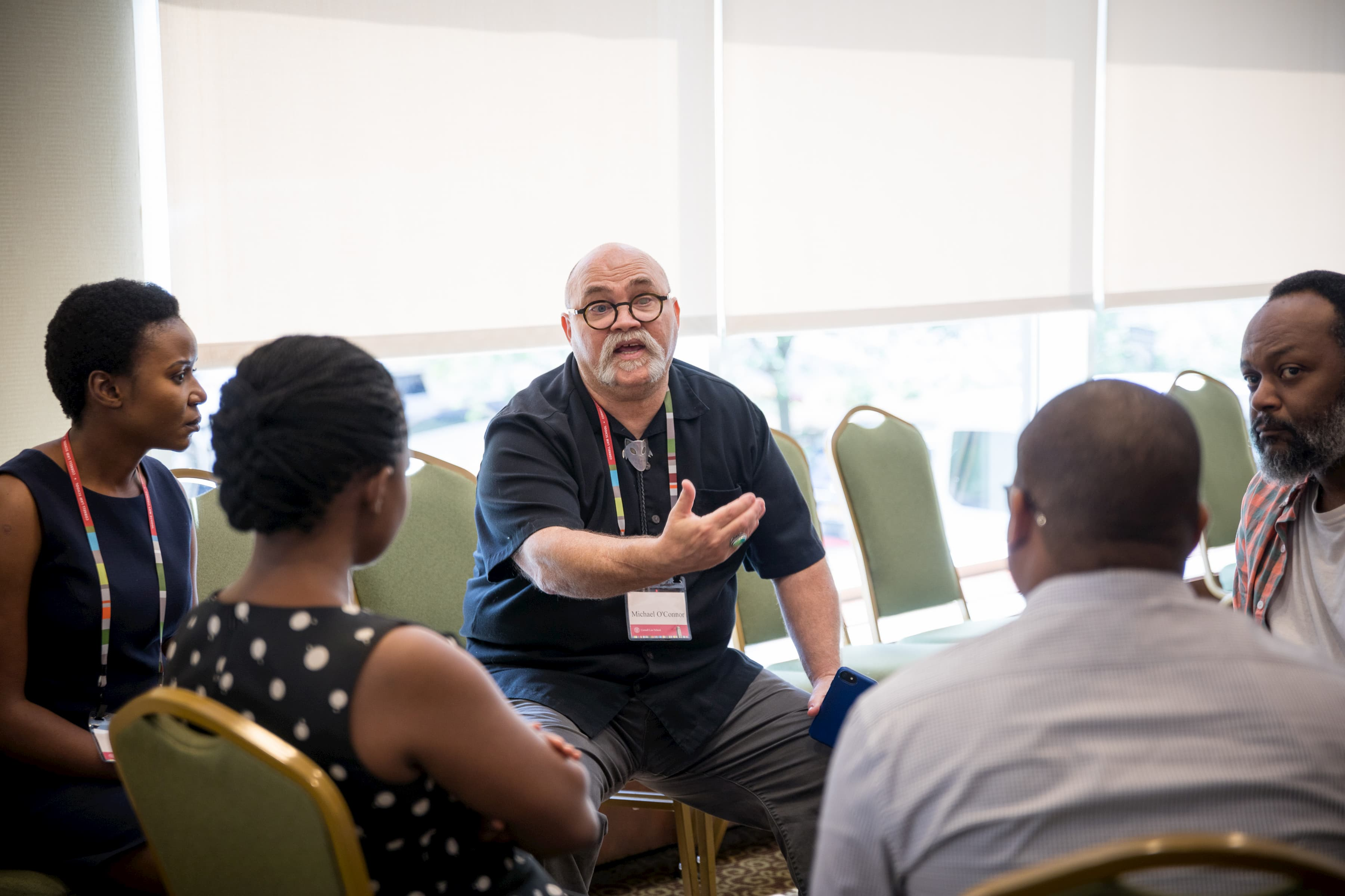 Un homme portant des lunettes et une chemise noire parlent. Quatre personnes autour de lui l'écoutent.