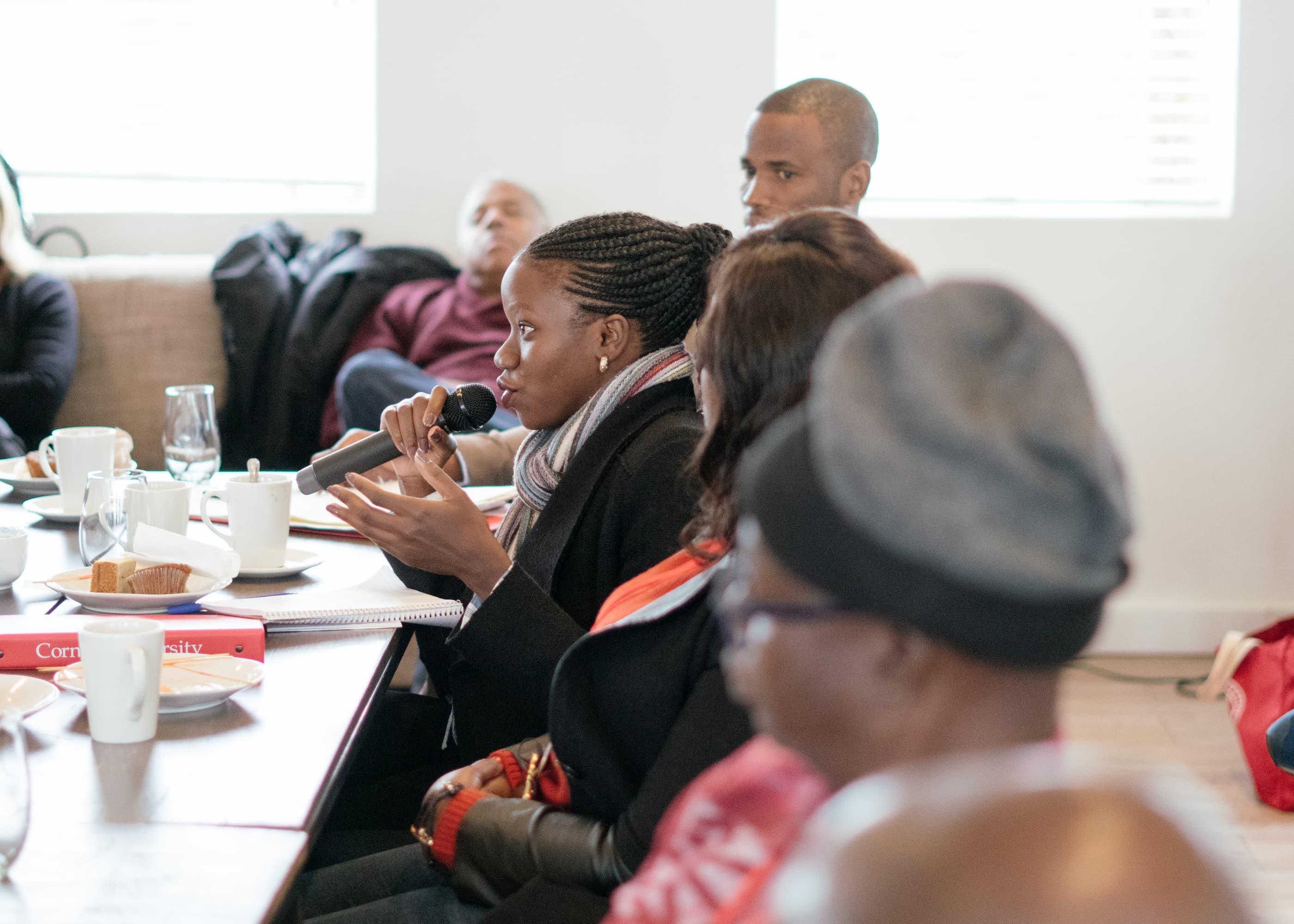 Une femme en veste noire est assise à une table et parle dans un microphone. D'autres, assis à la table, l'écoutent.
