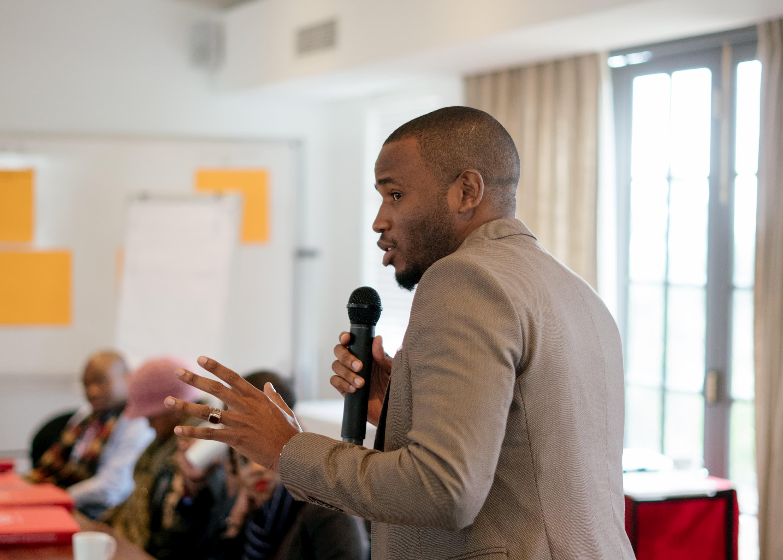 Un homme en veste beige est debout devant une salle et parle dans un microphone. Des personnes assises à une table l'écoutent.