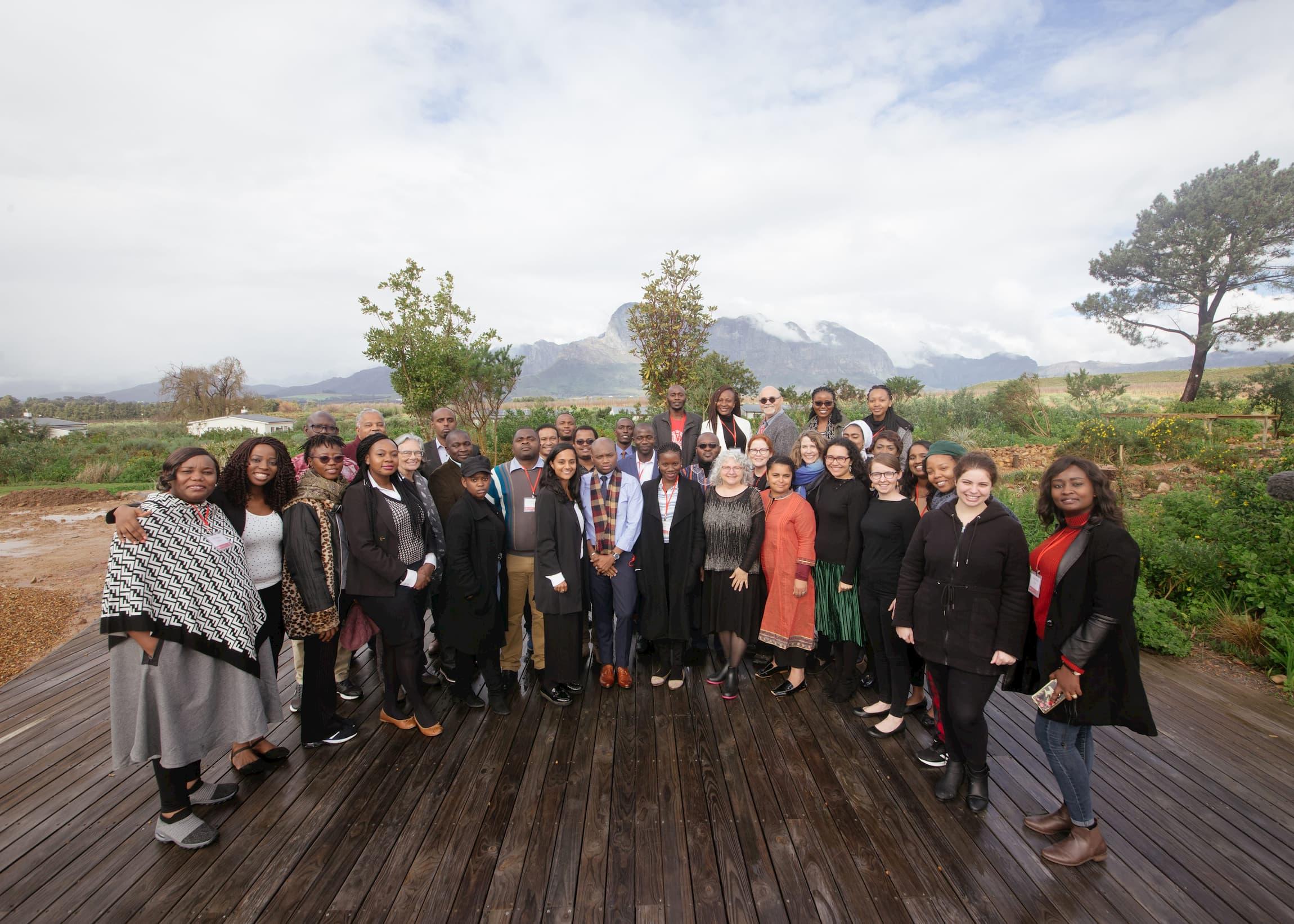 Un groupe d'environ quarante personnes pose pour une photo, debout en un demi-cercle à l'extérieur. Il y a des arbres et une grande montagne au loin derrière eux.