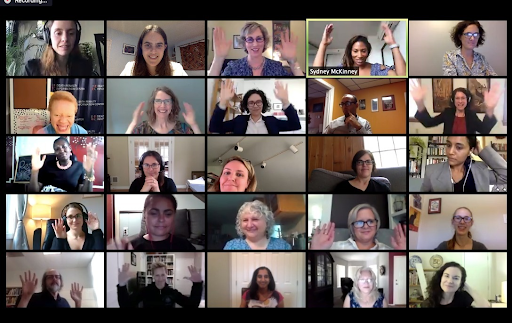 25 video conference participants smile. Several participants are raising up their hands.