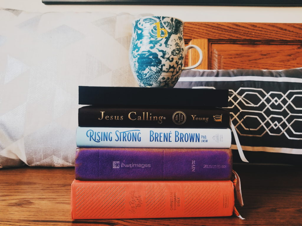 A stack of books used in my morning routine with a cup of coffee on top