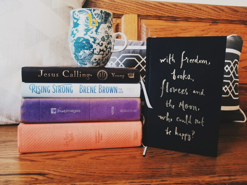 """Stack of books used for my morning quiet time routine with the Lord, with coffee on top and a book standing up right with the quote """"with freedom, books, flowers, and the moon, who could not be happy?"""""""