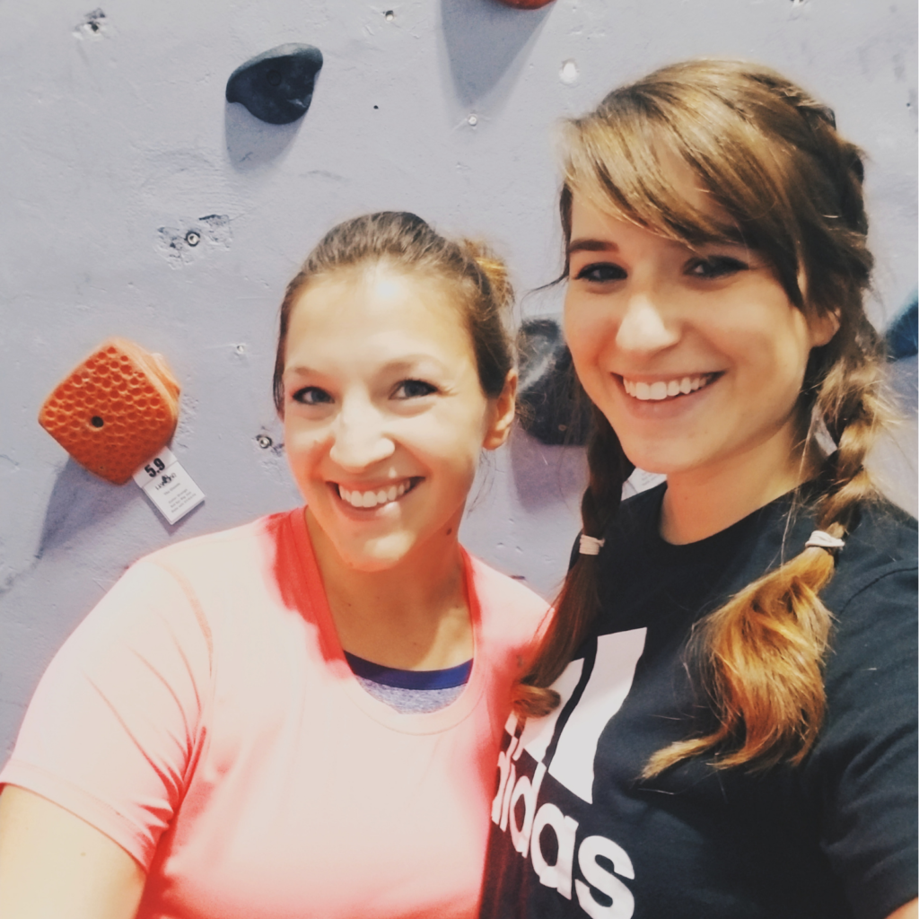 Two girls smiling, standing in front of a rock wall