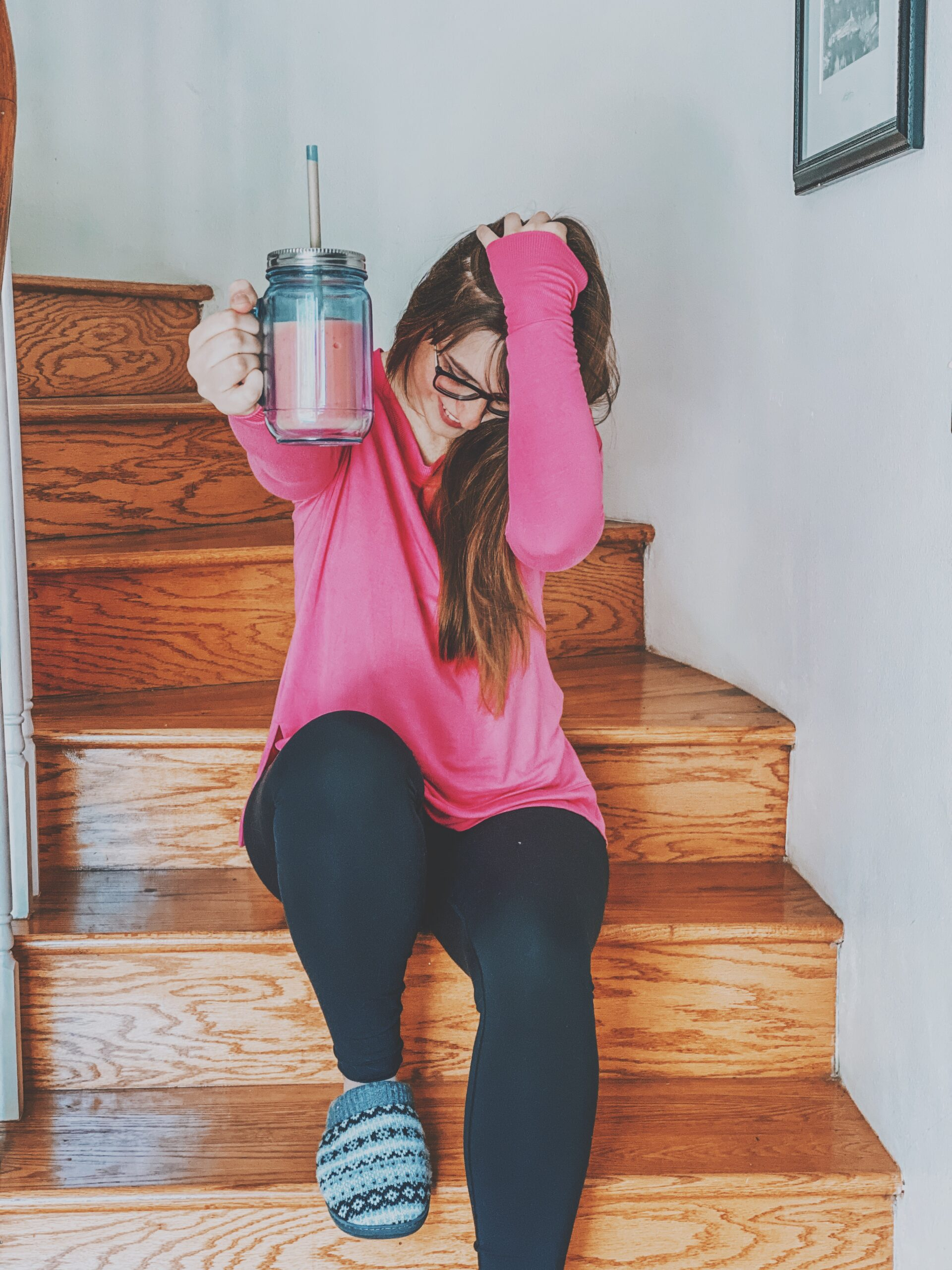 Girl holding up a pink smoothie