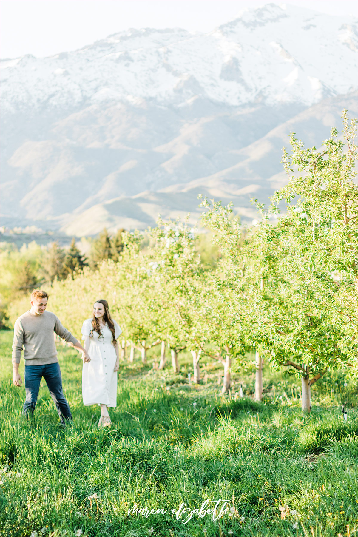Spring engagement pictures at Burgess Orchards in Alpine, UT with a perfect view of the mountains. | Maren Elizabeth Photography