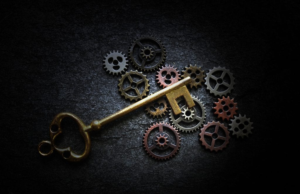 Antique key laying on vintage metal gears on a dark background