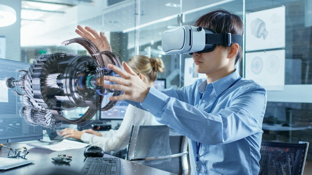 Male engineer wearing virtual reality headset and using hands to manipulate a 3D machine part model