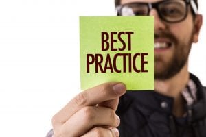 "A man holding up a yellow post-it with the word ""best practice"" on it."