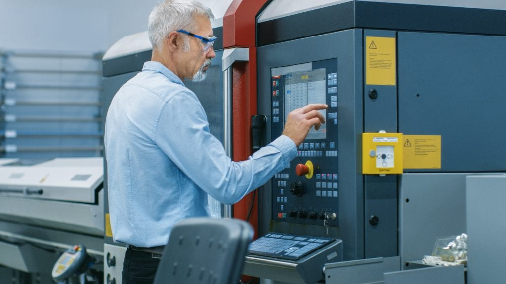 Older gentleman wearing a light blue shirt and safety glasses setting up a CNC machine using an electronic control panel.