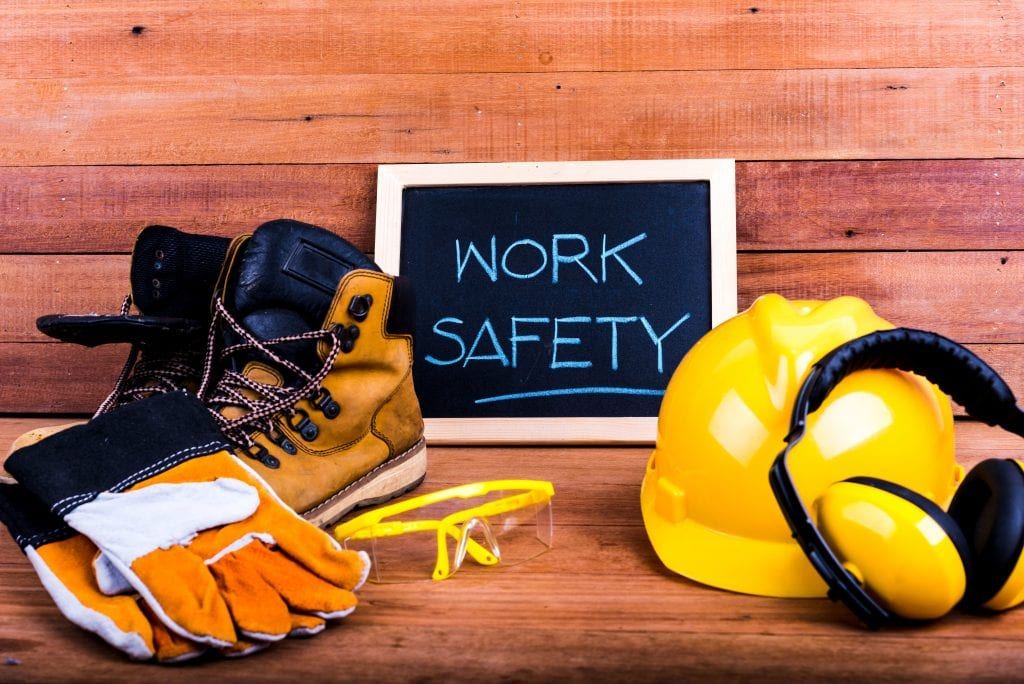 "gloves, work boots, safety goggles, hard hat on a wood plank background w/ ""work safety"" written on a framed chalkboard"
