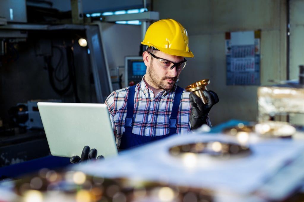Engineer wearing a yellow hard hat and safety glasses inspects a manufactured part while holding a laptop computer