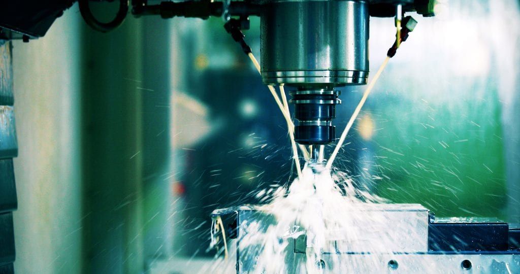Close up of CNC machine at work with coolant streams