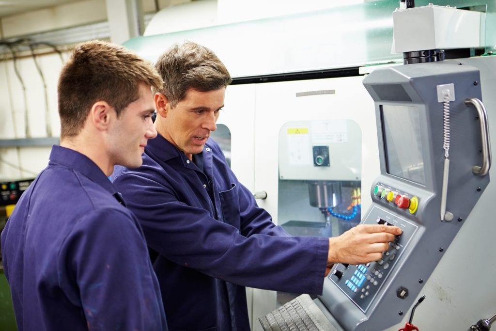 Two men adjusting the controls on an automated milling machine