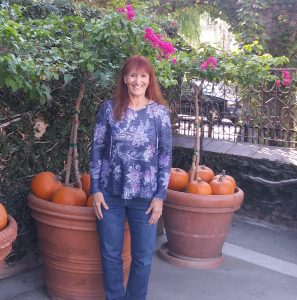 Ana Lash stands in front of plants and pumpkins