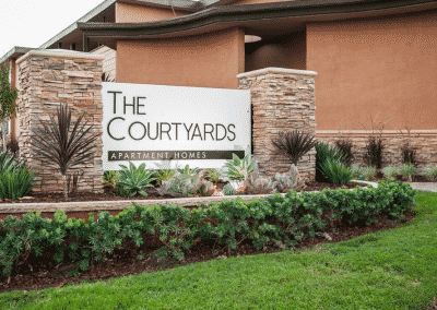 The Courtyards Apartment Homes entrance with sign and landscaping