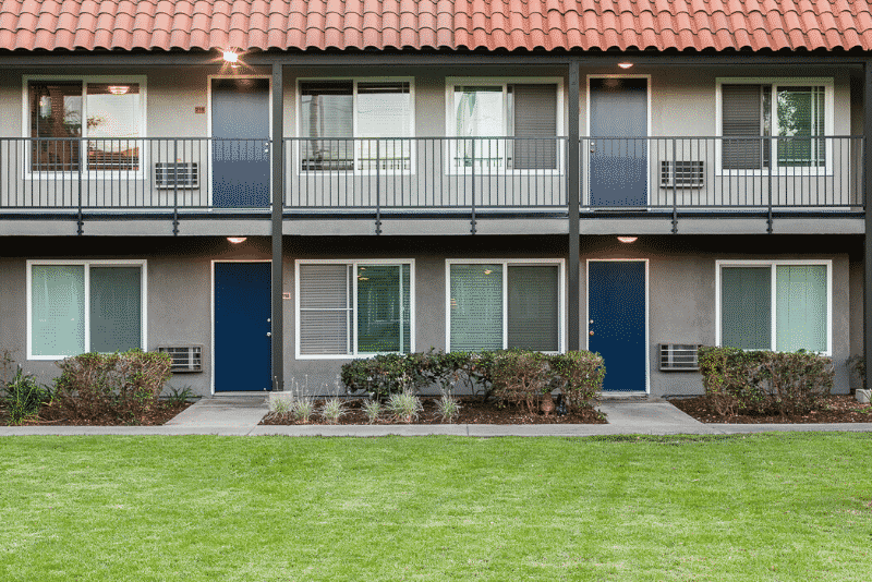 Two story apartment complex with blue doors