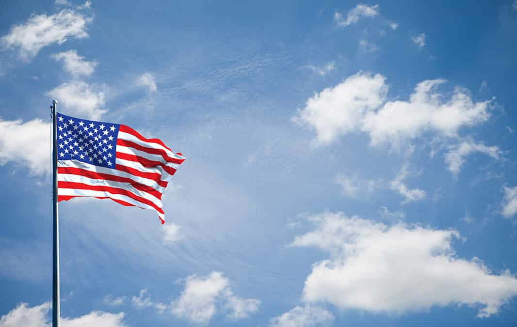American flag waving on the blue sky