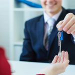 Young lady taking keys from male real estate agent during meeting after signing rental lease contract or sale purchase agreement. Independent woman purchasing new home, close up view